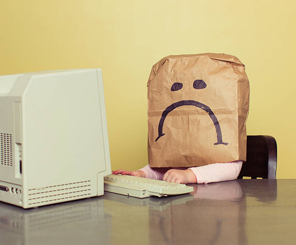 young girl in front of computer with brown bag frown - kids online abuse stockfoto's en -beelden