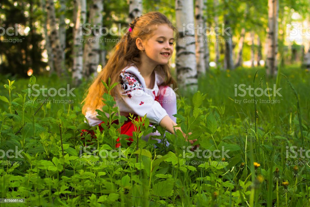 Young girl in garden with flowers and birches stock photo
