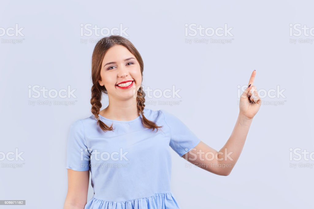 Young girl in glasses with pigtails with positive emotion points stock photo