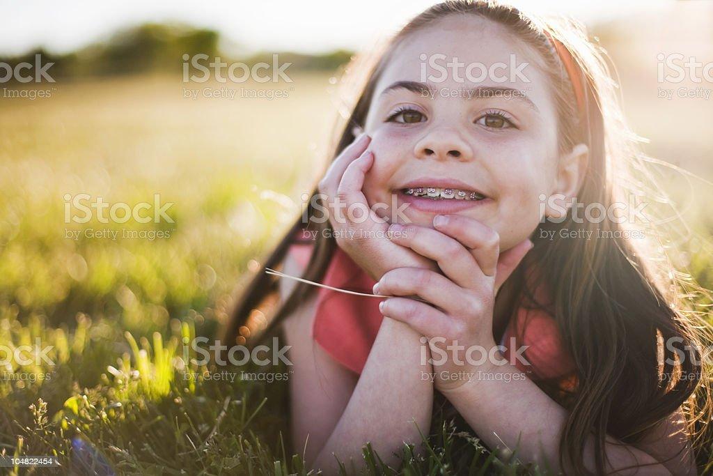 Junges Mädchen im Gras lächelnd – Foto