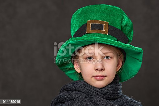 pretty young girl in green leprechaun hat with golden buckle and grey knitted scarf
