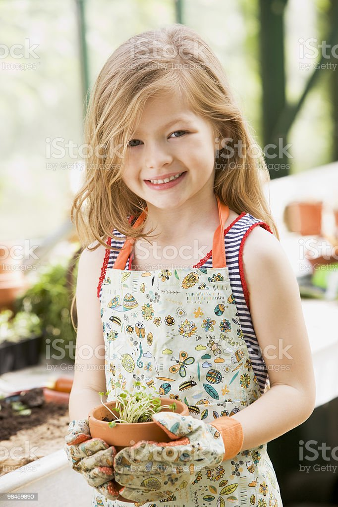 Young girl in greenhouse holding potted plant royalty-free stock photo