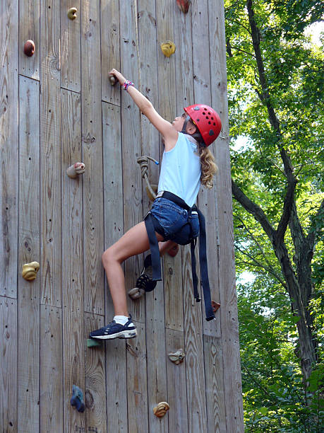 Young girl in helmet climbing a wooden wall with footholds stock photo