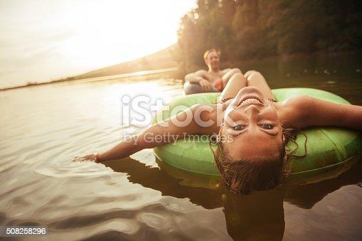 istock Young girl in lake on innertube 508258296