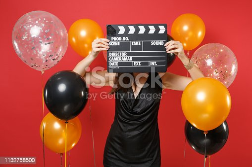 istock Young girl in little black dress covering face with classic black film making clapperboard on bright red background air balloon. Valentine's Day, Happy New Year, birthday mockup holiday party concept. 1132758500