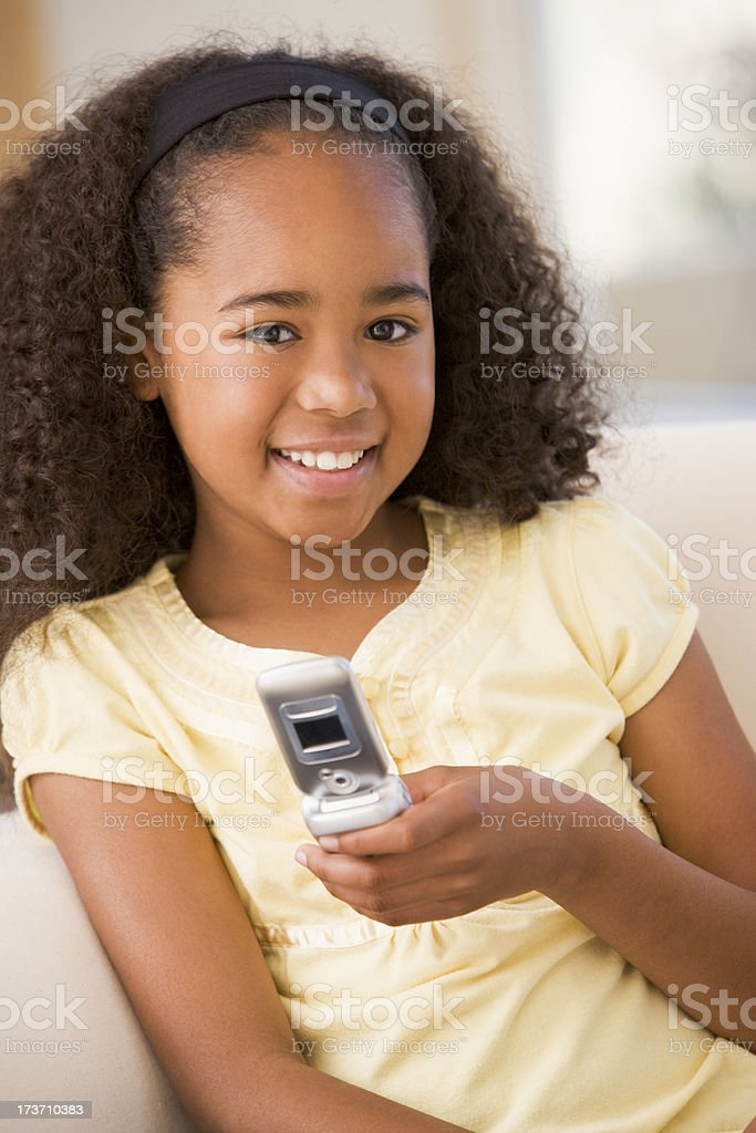 Young girl in living room using cellular phone and smiling royalty-free stock photo