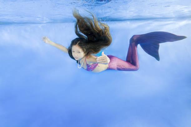 Young girl in mermaid costume wearing poses underwater in the pool, Odessa, Ukraine stock photo