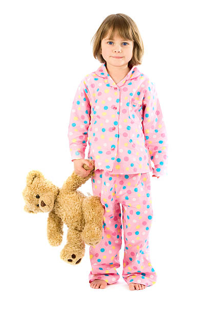 Young girl in pajamas with teddy bear on white stock photo