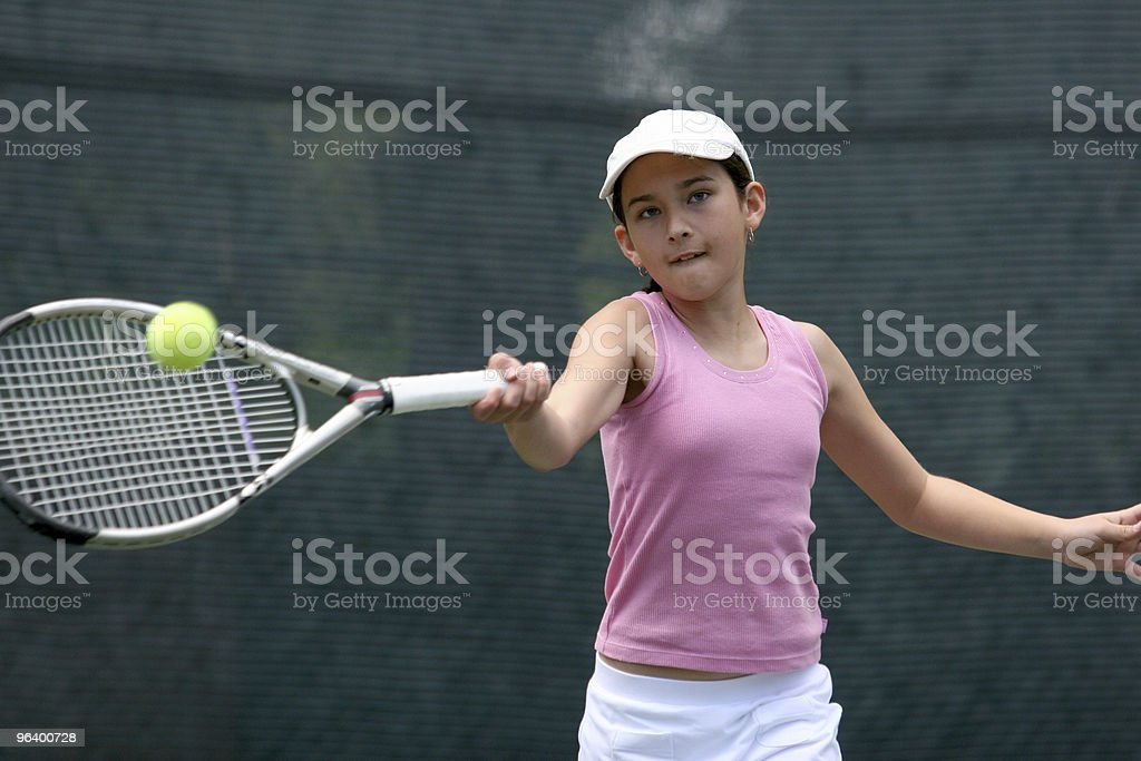A young girl in pink and white playing tennis outdoors stock photo