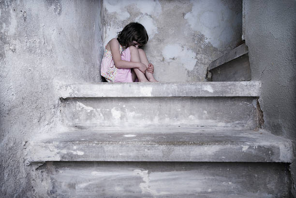 A young girl in pink cowering at the top of the stairs stock photo