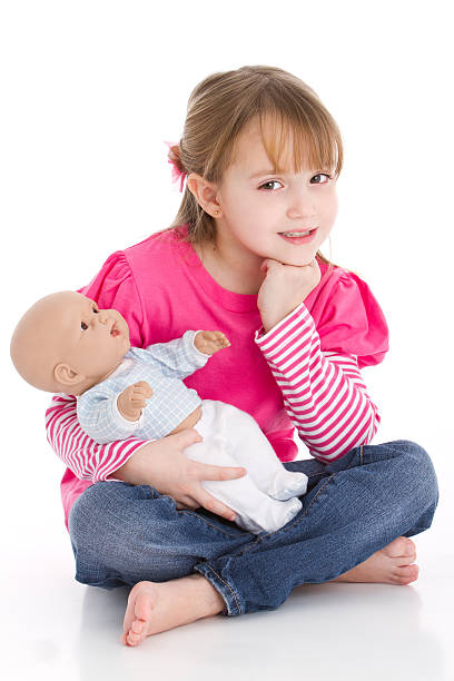 Young girl in pink sitting on floor and holding a baby doll stock photo