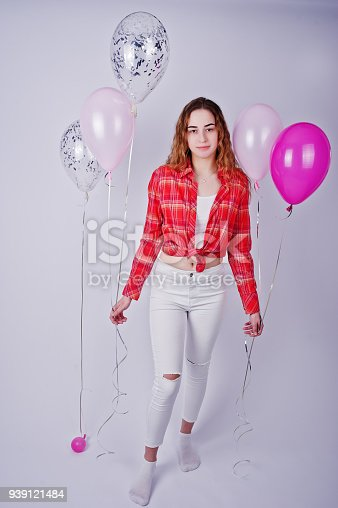 istock Young girl in red checked shirt and white pants with balloons against white background on studio. 939121484