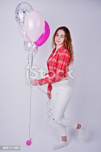 istock Young girl in red checked shirt and white pants with balloons against white background on studio. 939121490