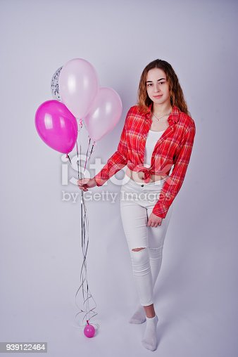 istock Young girl in red checked shirt and white pants with balloons against white background on studio. 939122464