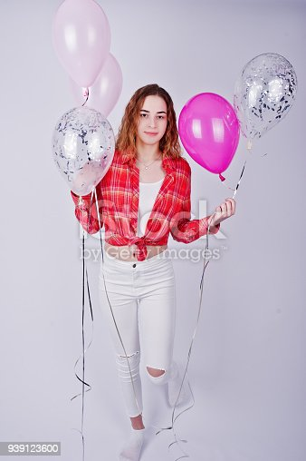 istock Young girl in red checked shirt and white pants with balloons against white background on studio. 939123600
