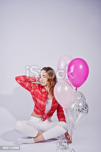 istock Young girl in red checked shirt and white pants with balloons against white background on studio. 939123686
