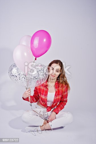 istock Young girl in red checked shirt and white pants with balloons against white background on studio. 939123722