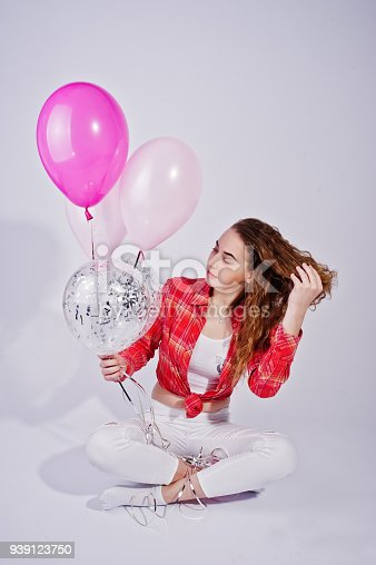 istock Young girl in red checked shirt and white pants with balloons against white background on studio. 939123750