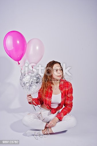 istock Young girl in red checked shirt and white pants with balloons against white background on studio. 939123782