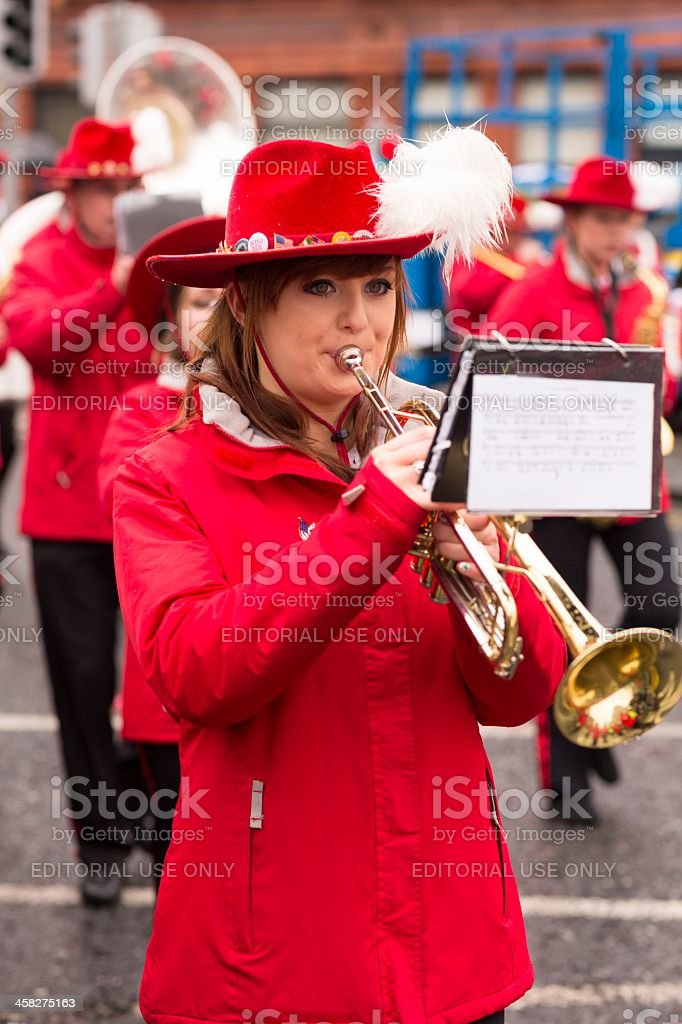 Young girl in red clothing playing on trumpet royalty-free stock photo