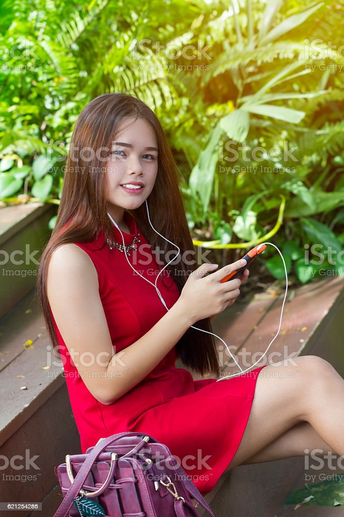 Young girl in red dress using smartphone stock photo