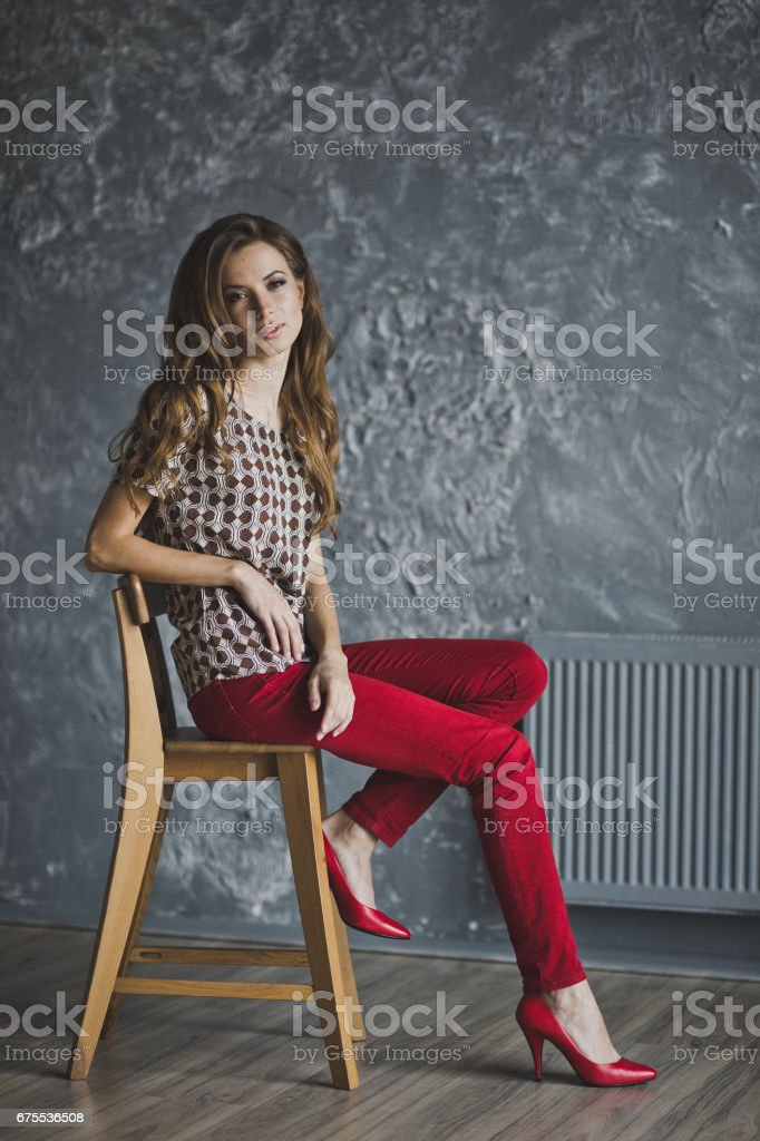 Young girl in red jeans was sitting on a chair 6945. photo libre de droits