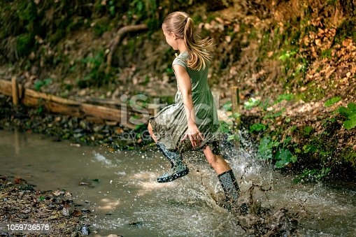 Young girl in rubber boots running across stream in the forest.