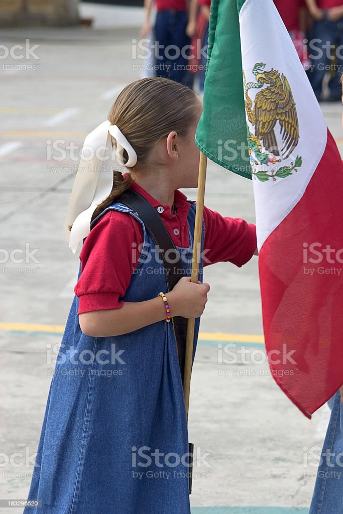 Young girl in school uniform holding the Mexican flag royalty-free stock photo