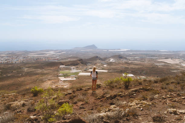 Young girl in shorts walking on the top of the hill - fotografia de stock