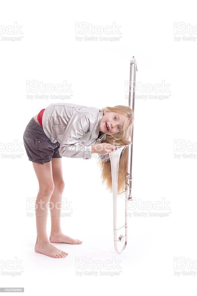 young girl in silver jacket having fun with  trombone stock photo