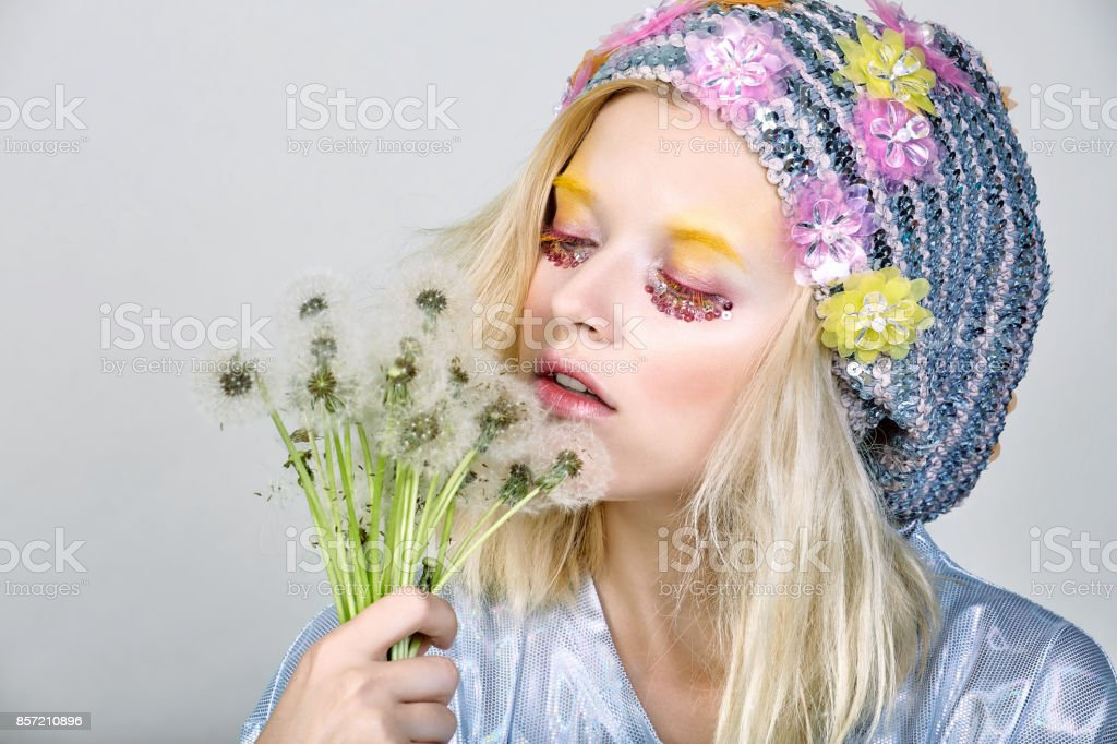 Young girl in sparkling hat with dandelions stock photo