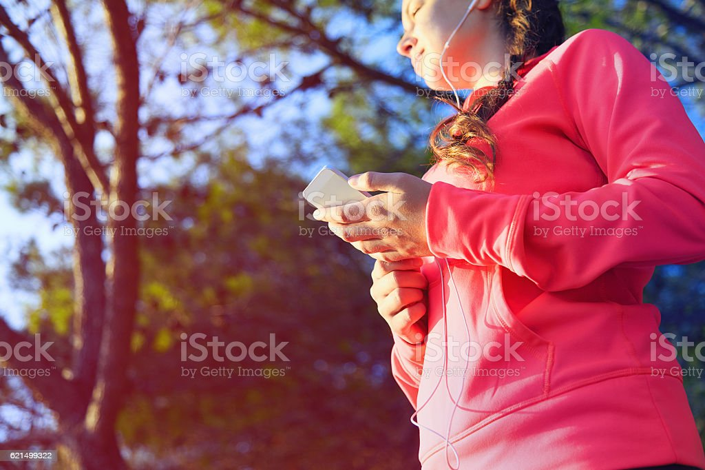 Young girl in sport outfit using her smartphone foto stock royalty-free
