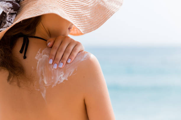 Young girl in straw hat is applying sunscreen on her back to protect her skin Young girl in straw hat is applying sunscreen on her back to protect her skin. suntan lotion stock pictures, royalty-free photos & images