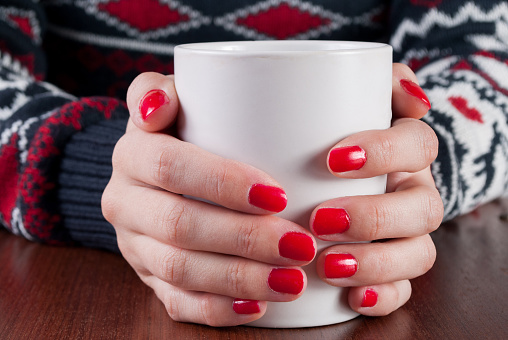 Young girl in sweater holding white coffee cup in hand with red nail on wooden desk