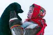 A young girl, in the national winter clothes of the northern inhabitants of the tundra, plays with a dog