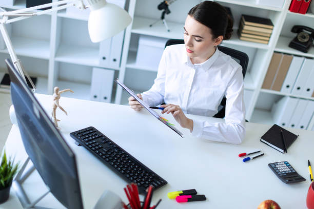 A young girl in the office holds a pen in her hand and works with documents and a computer. stock photo