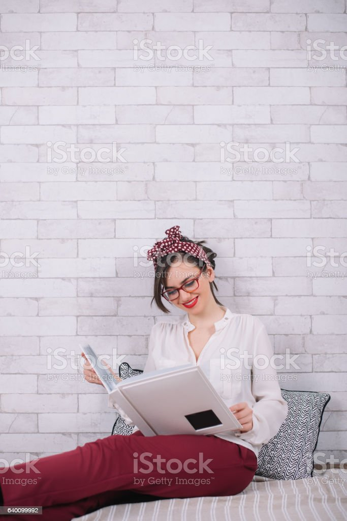 Young girl in vintage clothes looking at a photo album stock photo