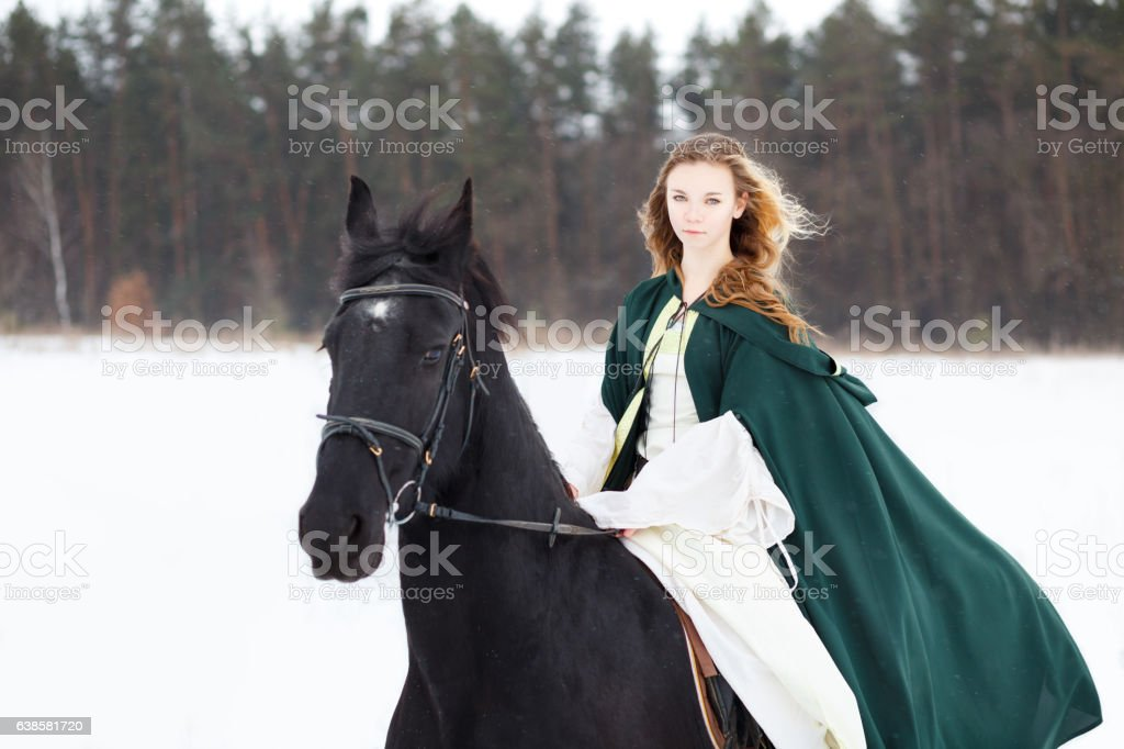 Young girl in white dress and cape riding horse stock photo