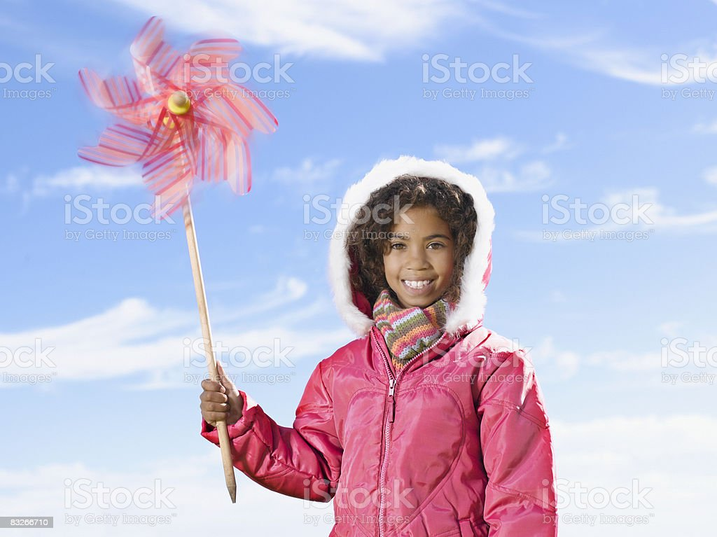 Young girl in winter coat holding spinning pinwheel royalty free stockfoto