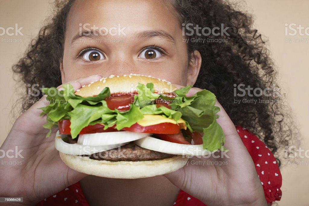 Young girl indoors eating a hamburger stock photo