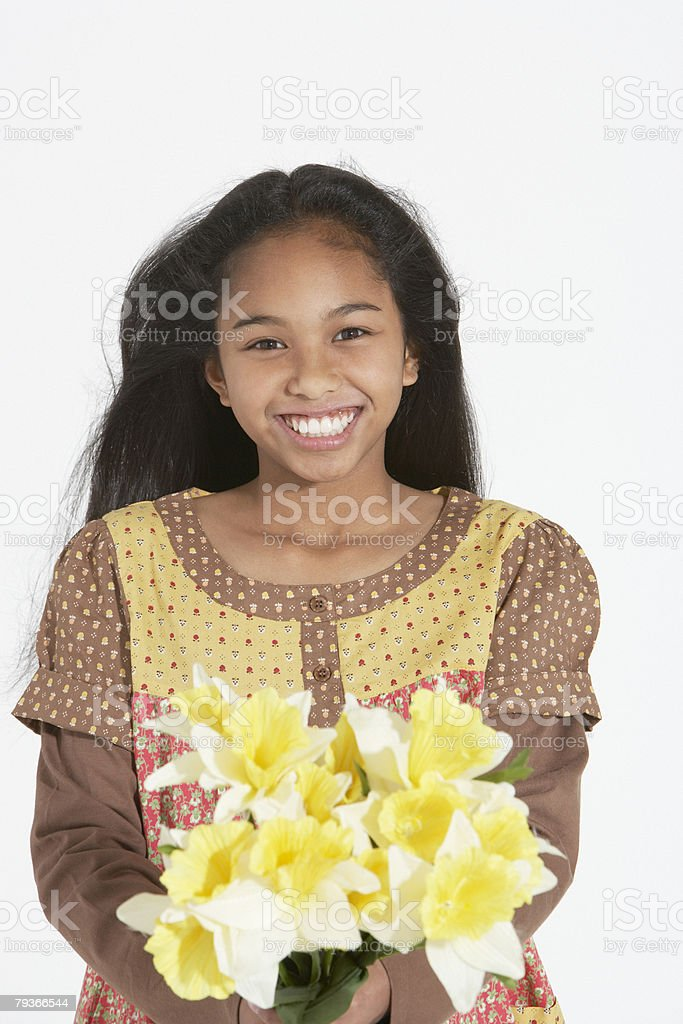 Young girl indoors holding a bouquet of flowers royalty-free stock photo