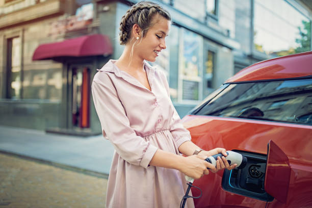 young girl is charging her electric car in the city - macchina ibrida foto e immagini stock