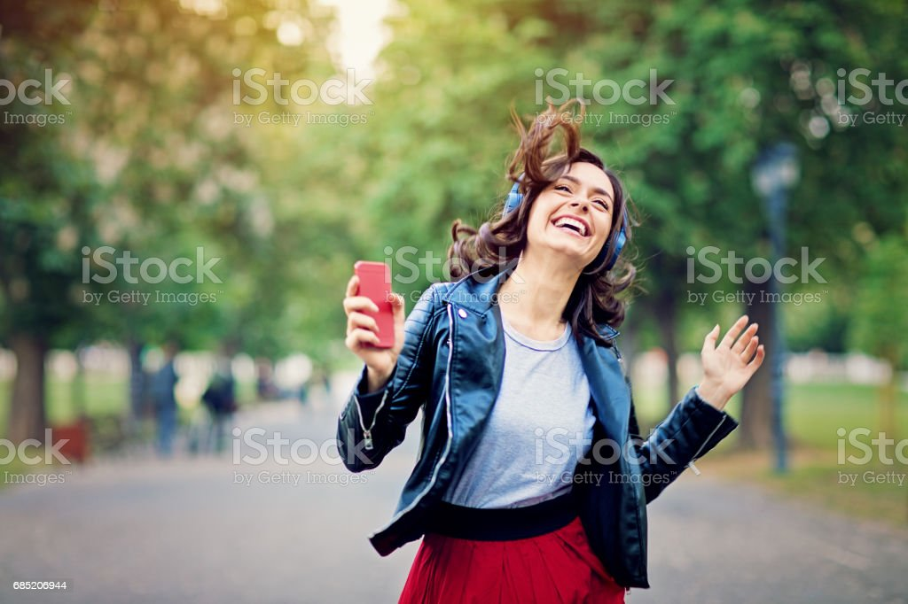 Young girl is dancing and listening the music till walking in the park stock photo
