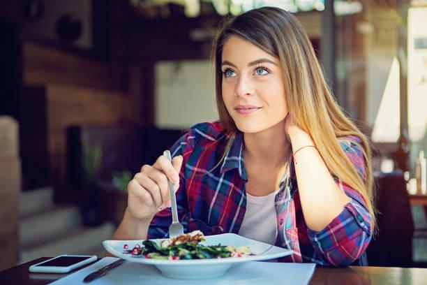 ung flicka äter sallad i restaurangen - tallrik uppätet bildbanksfoton och bilder