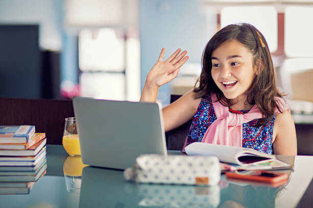 Young girl is e-learning and video conferencing at home stock photo
