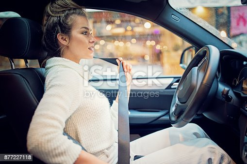 Young girl is fastening her seat belt in a rainy day