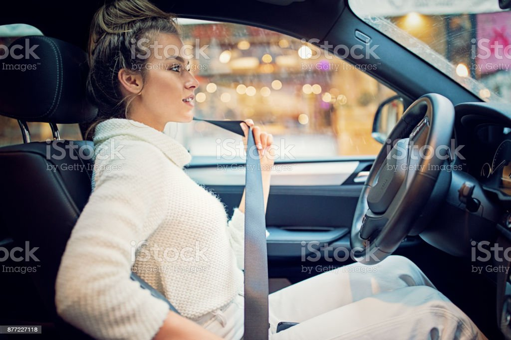 Young girl is fastening her seat belt in a rainy day stock photo