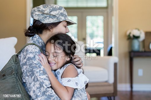 Relieved little girl hugs her mom after her mom's return home from military service.