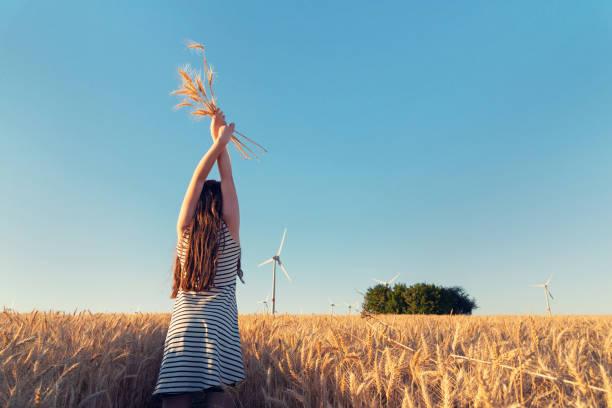 Junges Mädchen hält ein Getreide-Bouquet infront von Windkraftanlagen – Foto