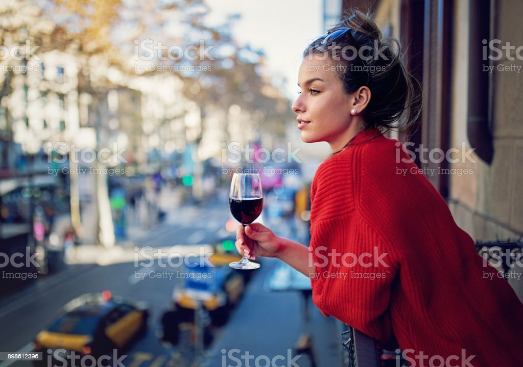 Young girl is looking the city at the balcony and drinking red wine royalty-free stock photo